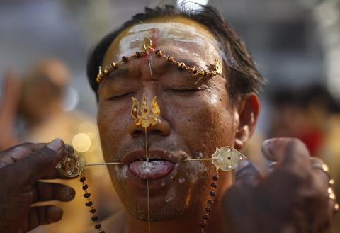 An ethnic Chinese devotee has his tongue pierced during Thaipusam festival in Singapore early January 17, 2014. Thaipusam is a Hindu festival observed on the day of the full moon during the Tamil calendar month of Thai, and celebrated in honour of the Hindu god Lord Murugan.