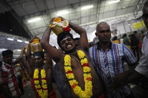 A devotee falls into trance as he carries a milk jug during Thaipusam festival in Singapore early January 17, 2014. Thaipusam is a Hindu festival observed on the day of the full moon during the Tamil calendar month of Thai, and celebrated in honour of the Hindu god Lord Murugan.