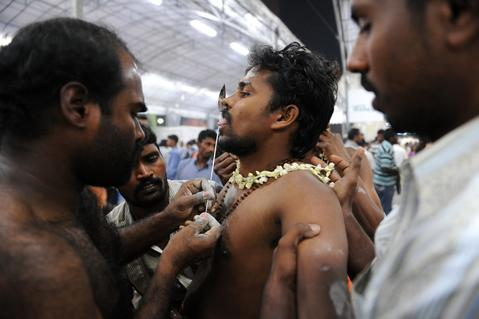 A Hindu devotee's tongue is pierced before a procession for the Thaipusam Hindu festival in Singapore, in the early hours of January 17, 2014. Thaipusam is celebrated during the full moon in the Tamil month of Thai and commemorates the birthday of the Hindu deity Murugan.