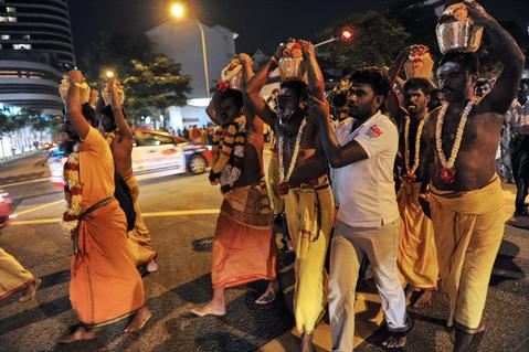 Hindu devotees carry pots of milk over their heads as part of a procession for the Thaipusam Hindu festival in Singapore, in the early hours of January 17, 2014. Thaipusam is celebrated during the full moon in the Tamil month of Thai and commemorates the birthday of the Hindu deity Murugan.