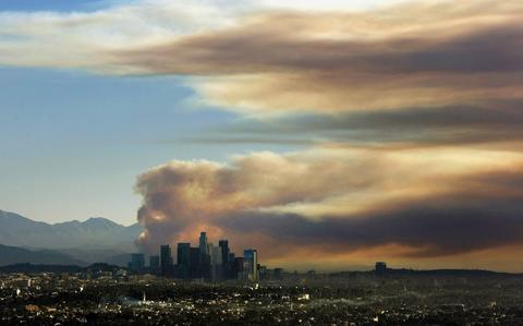 A large fire plume rises above the downtown skyline from the fast-growing Colby fire in Southern California from the Baldwin Hills Scenic Overlook Thursday morning, Jan. 16, 2014.