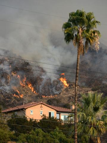 Flames burn near a home during the Colby Fire, January 16, 2014 in Azusa, California. The fast-moving Colby Fire originated early on Thursday in the San Gabriel Mountains just north of Glendora, about 30 miles (48kms) northeast of Los Angeles. Nearly 900 homes were evacuated Thursday after a wildfire scorched forests near Los Angeles, and cast a plume of smoke over the city, police said. Glendora police detained three men who allegedly set a campfire which sparked the blaze, shortly before 6:00 am (1400 GMT).