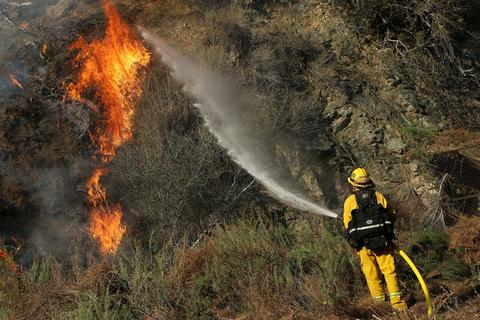 Firefighter Jeff Newby sprays water on a flare-up at the Colby Fire burning for a second day in the hillside above Highway 39 on January 17, 2014 in Azusa, California. The so-called Colby Fire, has burned about 1,700 acres in the Angeles National Forest north of Glendora and Azusa.