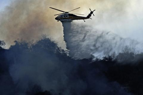 A firefighting helicopter makes a water drop on the Colby Fire burning for a second day in the hillside above Highway 39 in Azusa, California. Three men have been arrested and charged with starting the fire that has now destroyed 1,700 acres of land and several homes around Glendora and Azusa in the San Gabriel Valley, prompting officials to order evacuations for houses near the fire.