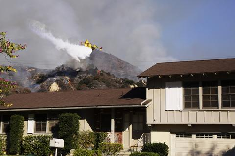 A plane drops water in an attempt to control wildfires burning through hillsides on January 16, 2014 in Azusa, California. Authorities have stated that three people have been charged with recklessly lighting a fire as the blaze known as the Colby Fire has now destroyed 1,700 acres of land and several homes around Glendora and Azusa in the San Gabriel Valley, prompting officials to order evacuations for houses near the fire.