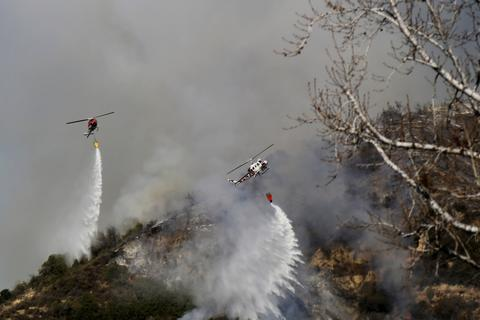 Helicopters work to control wildfires as they burn through hillsides on January 16, 2014 in Azusa, California. Authorities have stated that three people have been charged with recklessly lighting a fire as the blaze known as the Colby Fire has now destroyed 1,700 acres of land and several homes around Glendora and Azusa in the San Gabriel Valley, prompting officials to order evacuations for houses near the fire.