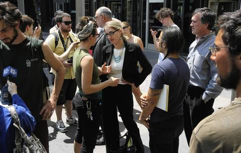 """Attorney Sarah Gelsomino, center, talks with activists outside the Cook County Courthouse in May following a hearing for the """"NATO 3."""""""