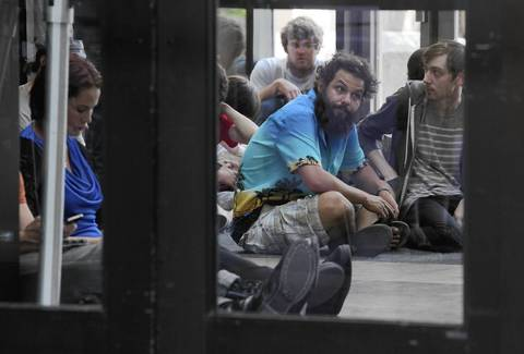 """Protesters wait in the lobby of the Cook County Courthouse in May 2012 during a hearing for the """"NATO 3""""."""