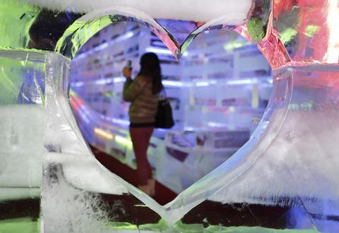 "A visitor taking photos at ""Fantasy Ice World"" behind a heart shaped ice sculpture on January 23, 2014 in Taipei, Taiwan."