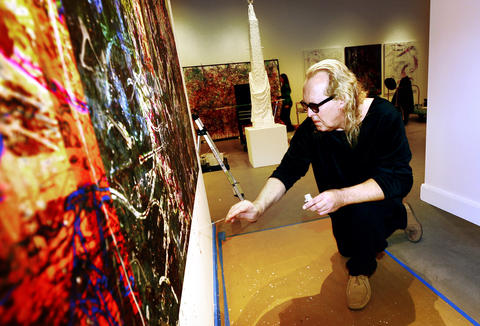 Artist Paul Harryn paints one of his works that is directly on a wall at the Allentown Art Museum.