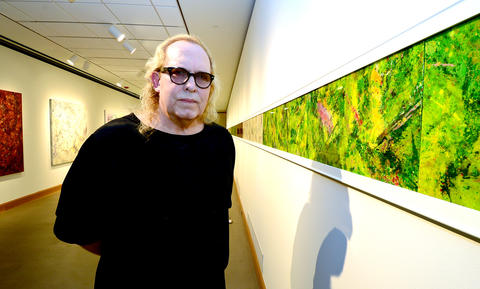 Artist Paul Harryn poses with one of his paintings that spans the length of a museum wall.   Paul Harryn is having a show at the Allentown Art Museum.