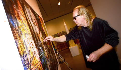 Artist Paul Harryn paints one of his works that is directly on a wall at the Allentown Art Museum.   Paul Harryn is having a show at the Allentown Art Museum.