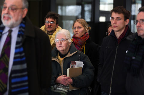 """Regina Bambrick-Rust, center in rear, stands with other supporters of the """"NATO 3"""" as Michael Deutsch, a lawyer for the People's Law Office who represents Brian Church, speaks to the media at the Leighton Criminal Court Building in Chicago."""