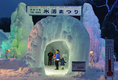 Visitors take picture in a welcome gate of the Chitose-Lake Shikotsu Ice Festival in Chitose, Hikkaido prefecture on January 24, 2014.