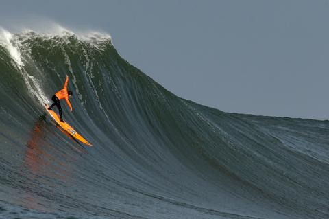 Tyler Fox rides a wave during the second heat of round one of Mavericks Invitational on January 24, 2014 in Half Moon Bay, California.