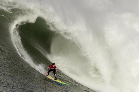 Colin Dwyer rides a wave during the second heat of round one of Mavericks Invitational on January 24, 2014 in Half Moon Bay, California.