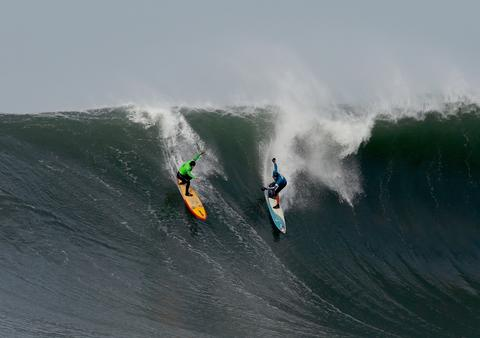 Danilo Couto (L) and Peter Mel share a wave during the second heat of round one of Mavericks Invitational on January 24, 2014 in Half Moon Bay, California.
