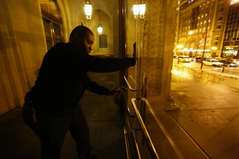 Maurice Tanner, a daytime security officer at the Art Institute of Chicago, locks the first row of Michigan Avenue entrance doors as the museum closes down for the night.
