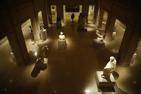 At closing time, one of the last visitors to the Art Institute of Chicago passes through a court featuring early American sculptures.
