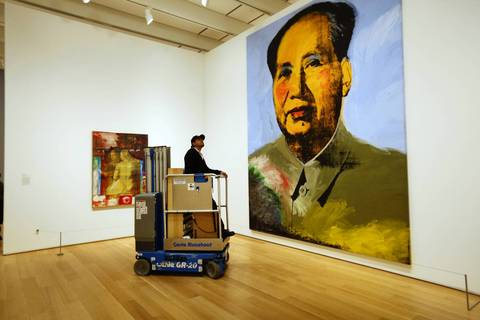 """Before opening, electrician Jaime Govea rides a scissor-lift Friday, Dec. 20, 2013 through the Modern Wing of the Art Institute of Chicago, looking for light bulbs to replace. At right is """"Mao, 1973"""" by Andy Warhol."""