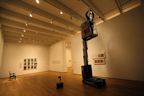 Electrician Jaime Govea, 29, uses a scissor-lift Friday, Dec. 20, 2013 in the Modern Wing of the Art Institute of Chicago, replacing light bulbs efore the museum opens.