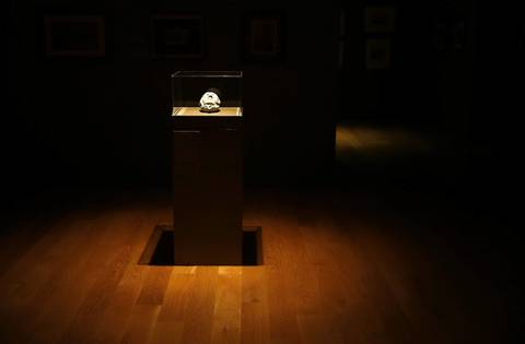 """""""Sleep (Female Mask with Closed Eyes)"""", from 1896, is lit alone Friday, Dec. 20, 2013 as other paper arts gallery lights are off. Lights in the paper arts are left off until just before opening to protect the artwork."""