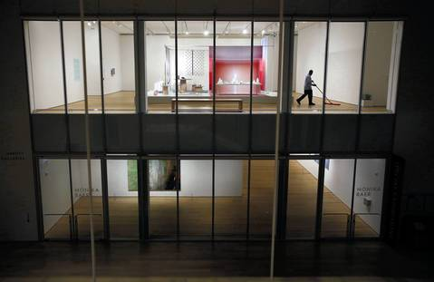 In the Modern Wing of the Art Institute of Chicago, a housekeeper dusts the floor in an exhibit in the architecture and design gallery after closing.