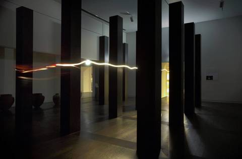 The beam of a flashlight carried by Michael Karczynski, evening shift security supervisor, trails between parts of a modern sculpture.