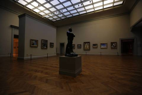 """The sculpture """"Portrait of Balzac,"""" by Auguste Rodin, holds court in the morning twilight in Gallery 201, lit only by a skylight before opening."""