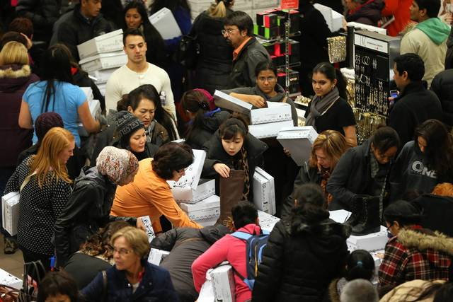 Shoppers look through boxes of Rampage shoes in the Macy's department store in Woodfield Mall in Schaumburg on Thanksgiving day in the evening.