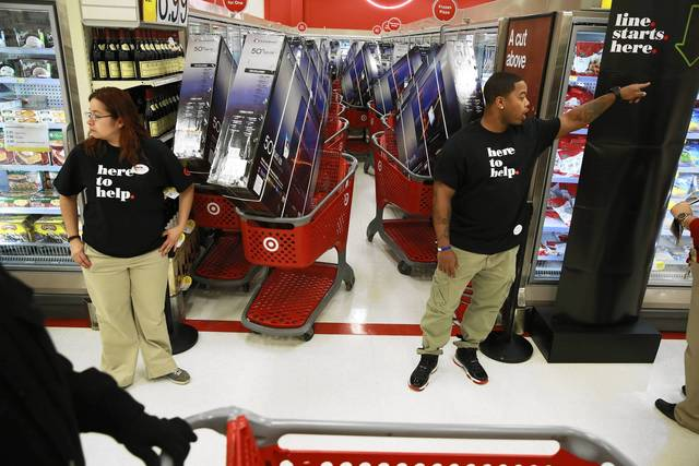 Employees guard carts loaded with televisions at a Target store on North Elston Avenue, which opened at 8 p.m. on Thanksgiving.