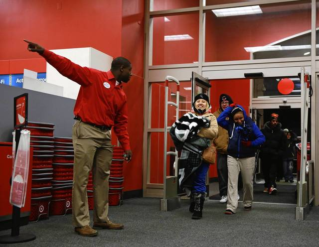 A store manager points to where the sale televisions are located as the first customers enter the Target store on North Elston Avenue in Chicago, which opened at 8 p.m. on Thanksgiving.