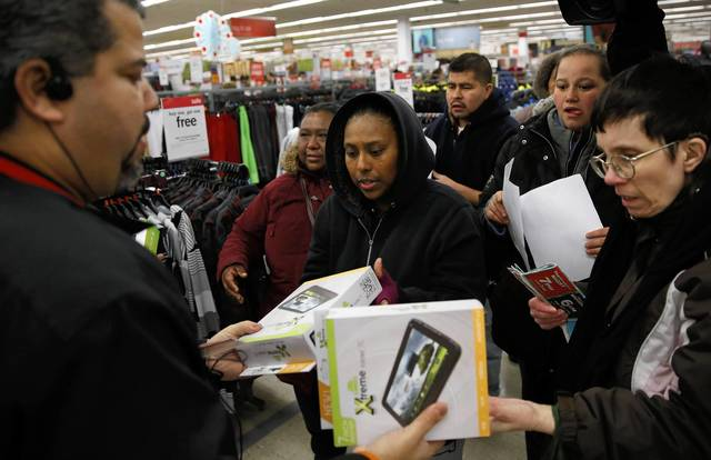Shoppers receive tablets from Rafael Silva, left, an assistant manager at Kmart in Chicago as the Thanksgiving shopping begins on Thursday.