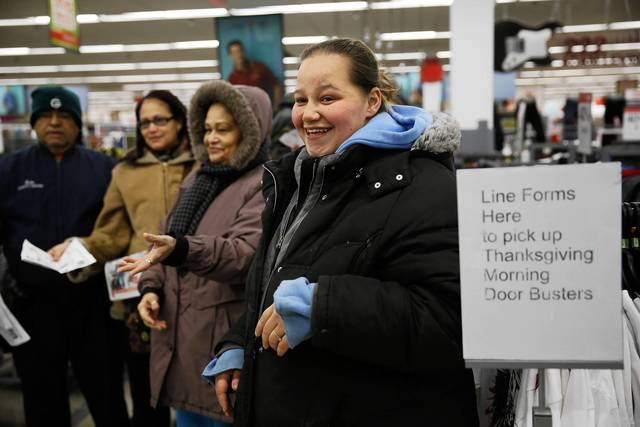 Stephanie Torres, right, waits to receive a large flat screen television and a tablet with other shoppers at a Kmart at 3443 W. Addison Street in Chicago on Thursday.