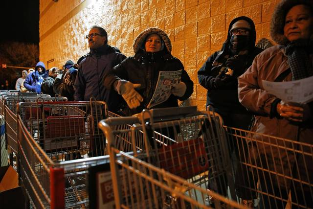 Luis Torres, fourth from right, and his daughter, Stephanie Torres, third from right, line up behind a row of shopping carts as people line up outside of Kmart at 3443 W. Addison Street in Chicago waiting for the doors to open on Thursday. Kmart is the only retail store opening first thing in the morning on Thanksgiving Day.