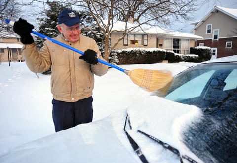 Ed Ryan, of Allentown, uses a broom to clean off his car Saturday after the snow stopped.