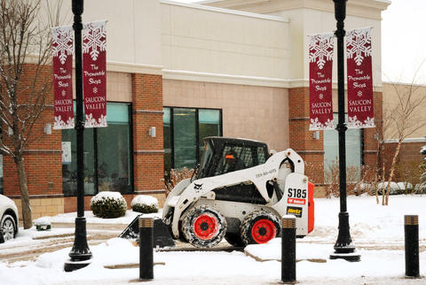 A bulldozer moves snow off the sidewalks Saturday at The Promenade Shops in Saucon Valley.