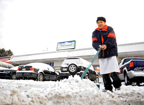 Teodoro Ro Luna helps clear the parking lot Saturday afternoon at Sophia's Pizza on Emmaus Avenue in Allentown as the snow cleared out.