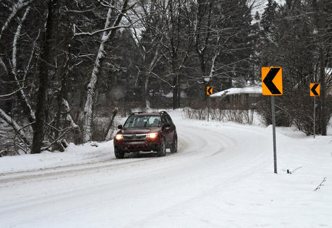 A car moves slowly down a snow cover Camp Meeting Road Saturday in Center Valley.