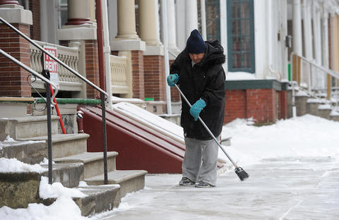 Carol Loper of Allentown clears the snow off of the sidewalk in front of her house along Chew street in Allentown on a snowy Saturday.