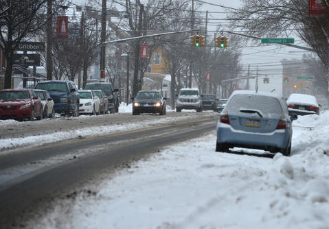 Vehicles slowly drive on Main Street. Roads are snowy and slushy in Emmaus on Saturday, January 25, 2014.