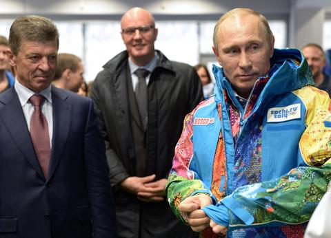 Russian President Vladimir Putin (R) tries an Olympic volunteers uniform, visiting an equipment centre in Sochi.