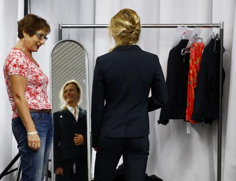 German Cross Country gold medallist Claudia Nystad (R) smiles as she checks the size of her official Olympic uniform for the Sochi Winter Olympic Games.