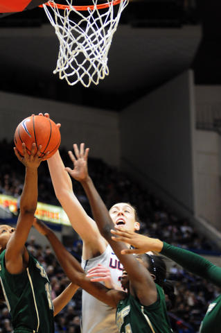 Breanna Stewart, at center, stretches for the ball during the first half of the game.