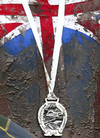 A competitor wears his medal after finishing the Tough Guy event in Perton, central England, January 26, 2014. The annual event to raise cash for charity challenges thousands of international competitors in a cross country run followed by an assault course consisting of obstacles including water, fire and tunnels.