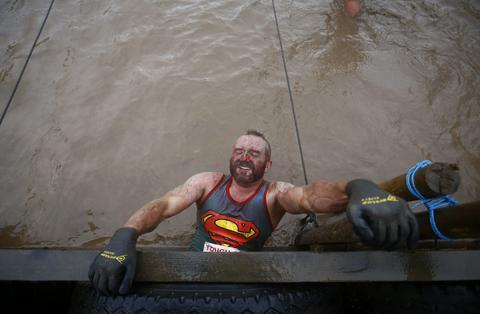A competitor hangs above muddy water during the Tough Guy event in Perton, central England January 26, 2014. The annual event to raise cash for charity challenges thousands of international competitors in a cross country run followed by an assault course consisting of obstacles including water, fire and tunnels.