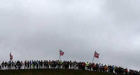Competitors line up beneath Union flags as they wait for the start of the Tough Guy event in Perton, central England January 26, 2014. The annual event to raise cash for charity challenges thousands of international competitors in a cross country run followed by an assault course consisting of obstacles including water, fire and tunnels.
