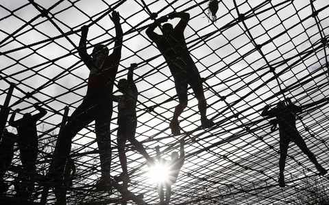 Competitors climb a cargo net during the Tough Guy event in Perton, central England, January 26, 2014. The annual event to raise cash for charity challenges thousands of international competitors in a cross country run followed by an assault course consisting of obstacles including water, fire and tunnels.