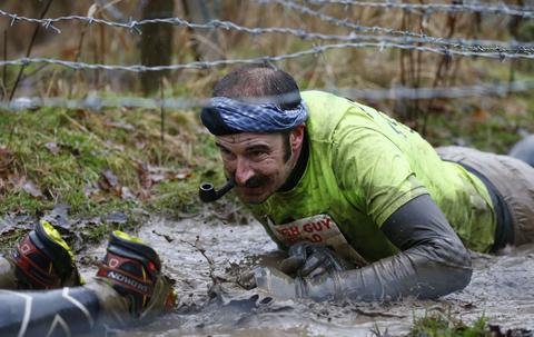 A competitor smokes a pipe as he crawls under barbed wire during the Tough Guy event in Perton, central England, January 26, 2014. The annual event to raise cash for charity challenges thousands of international competitors in a cross country run followed by an assault course consisting of obstacles including water, fire and tunnels.