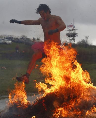 A competitor jumps across a burning obstacle during the Tough Guy event in Perton, central England January 26, 2014. The annual event to raise cash for charity challenges thousands of international competitors in a cross country run followed by an assault course consisting of obstacles including water, fire and tunnels.